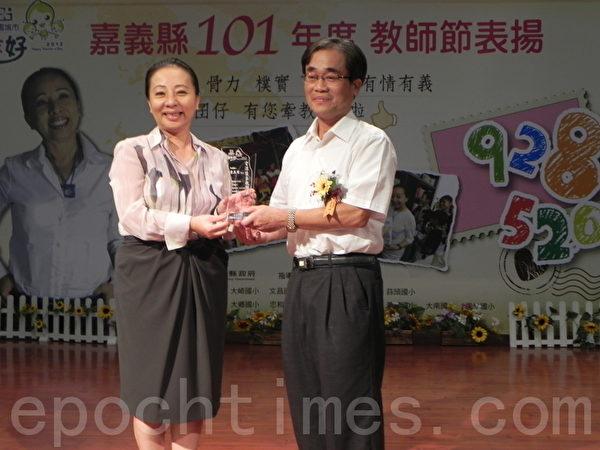在嘉义县庆祝101年教师节表扬大会中,连续服务届满40年的柳沟国小校长宋英明(右),在接受县长张花冠(左)表扬后表示,得这个奖是最容易的,只要坚持就能得到。(摄影:蔡上海/大纪元)