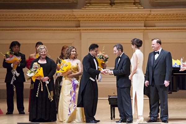 """西西里歌剧学院院长格罗索(William Grosso,右三)为第六届""""全世界歌剧唱法声乐大赛""""铜奖获得者颁奖。图为格罗索正在颁奖给铜奖得主之一来自马来西亚的男高音选手陈韦翰。(摄影:戴兵/大纪元)"""