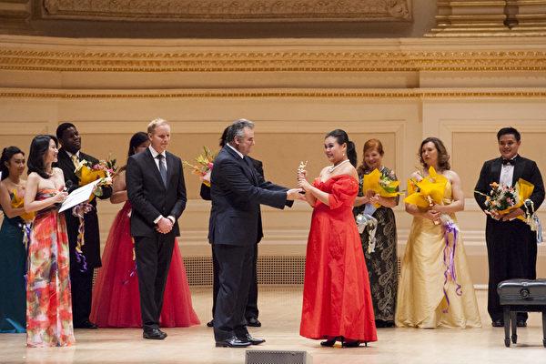 图:世界顶级歌剧演唱家马塞洛.乔达尼(Marcello Giordani)为女声金奖获得者——台湾选手左涵瀛颁奖。(摄影:戴兵/大纪元)