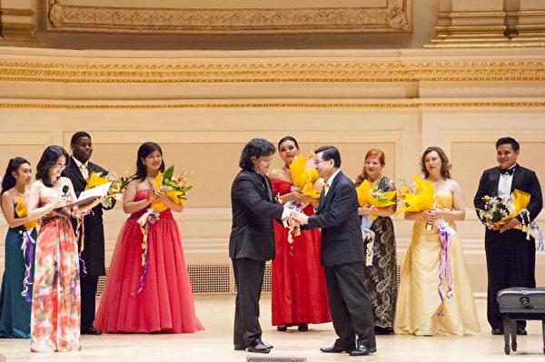 新唐人電視臺總裁李琮頒獎給第六屆「全世界歌劇唱法聲樂大賽」男聲組金獎得主——來自加拿大的選手男高音張洋。(攝影:戴兵/大紀元)