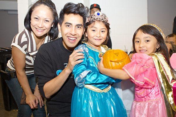 圖:迪斯尼冰上匯演的演員(左2)與孩子和家長開心度過萬聖派對。(攝影:李歐/大紀元)