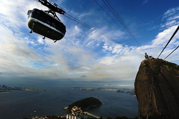 2012年,10月27日巴西里约热内卢名胜糖面包山的缆车欢庆100岁生日。图为游客搭乘糖面包山缆车可饱览瓜纳巴拉湾美丽景致。(ANTONIO SCORZA / AFP)