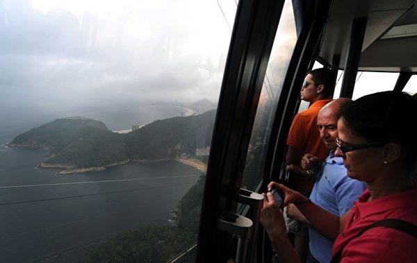 2012年,10月27日巴西里约热内卢名胜糖面包山的缆车欢庆100岁生日,游客搭乘糖面包山缆车可饱览360度的景色。(ANTONIO SCORZA / AFP)