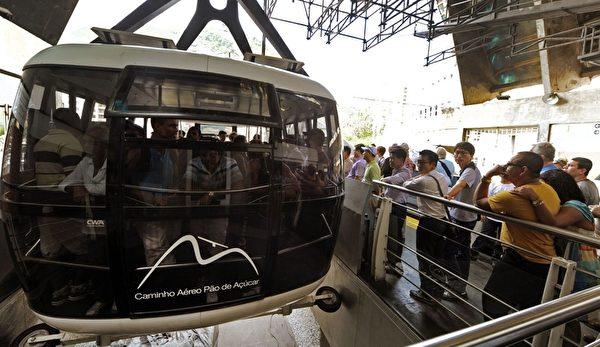 2012年10月27日,巴西里约热内卢名胜糖面包山的缆车欢庆100岁生日。图为游客排队搭乘糖面包山缆车。(ANTONIO SCORZA / AFP)