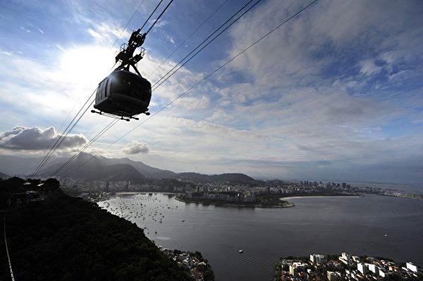 2012年,10月27日巴西里约热内卢名胜糖面包山的缆车欢庆100岁生日。图为糖面包山的缆车看起来像颗高挂空中的钻石。(ANTONIO SCORZA / AFP)