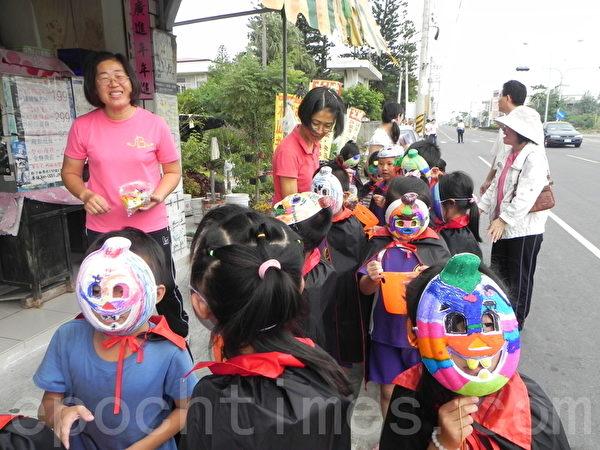 議員與學童彩繪變裝踩街活動中,社區商店、住家也共襄盛舉,致送糖果禮物給學童。(攝影:蔡上海/大紀元)