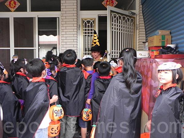 議員與學童彩繪變裝踩街活動中,嘉義縣長張花冠(面向鏡頭者)變裝為巫婆,被變裝的學童們包圍,大喊:「不給糖,就搗蛋。」(攝影:蔡上海/大紀元)