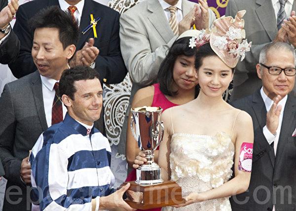今屆「莎莎婦女銀袋日」形象大使劉詩詩,致送紀念盃予冠軍馬匹「包裝博士」的騎師柏寶。(攝影:余鋼/大紀元)