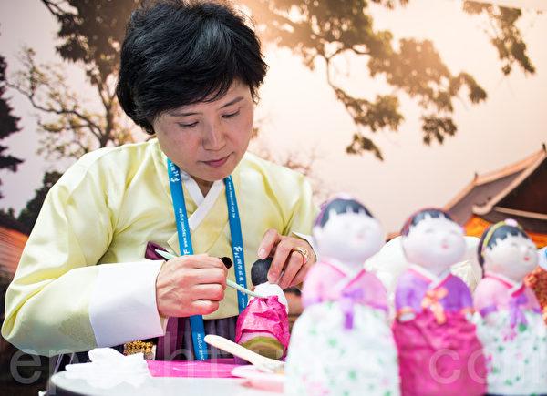 气质端庄的曹琼花用尊敬细心态度做韩纸人偶,韩纸韩国带来,楮树皮制作而成,具有不易掉色的特性;韩纸也常运用在一般韩国家庭的屏风跟壁纸之中。(摄影:陈柏州/大纪元)