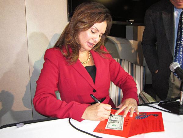 美國財政部財務長羅西‧里奧斯現場為大家在蛇年「吉利錢」上簽字。(攝影︰余雅妍/大紀元)