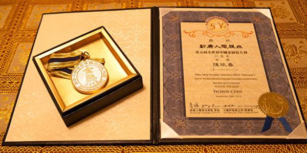 2012年新唐人「全世界中國菜廚技大賽」金獎獲得者陳依春先生的獲獎證書和獎章。(攝影:陳晨/大紀元)