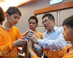 """台中启明的学生,在邓鸿吉(右2)引导下触摸多功能水杯,鼓励他们""""把想法想出来、说出来就对了!""""(摄影:黄玉燕/大纪元)"""