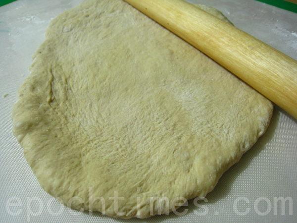 将已发酵之面团分割成2团,再分别杆平。(摄影: 杨美琴/ 大纪元)