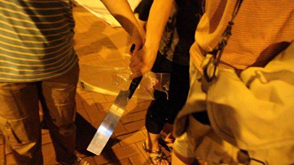 """7月4日晚,""""香港青年关爱协会""""在中港边境落马洲出动锯刀等械具,恐吓在场的法轮功学员和采访记者,而在场警员却袖手旁观不作为。图为一名穿间条衫的女凶徒一度从另一名协会徒众手上接过锯刀,准备趋前恐吓记者。(摄影:蔡雯文/大纪元)"""