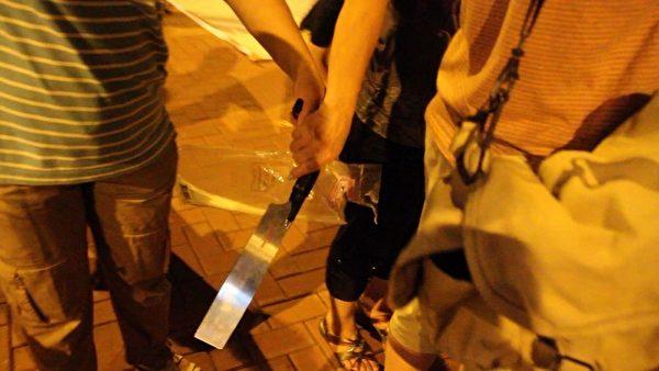 今年7月4日晚,青关会成员在落马洲出动锯刀,涉嫌恐吓在场的法轮功学员和采访记者,但现场的警察却以没有人受伤为由,只是登记在案,不作任何处理。(大纪元)