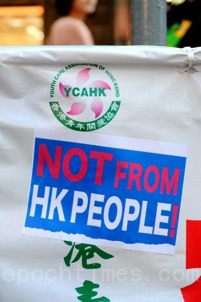 有市民響應「藉著貼紙踢爆你行動」,在青關會誣衊法輪功的橫幅上,貼上「NOT FROM HK PEOPLE!」的貼紙。(攝影:宋祥龍/大紀元)