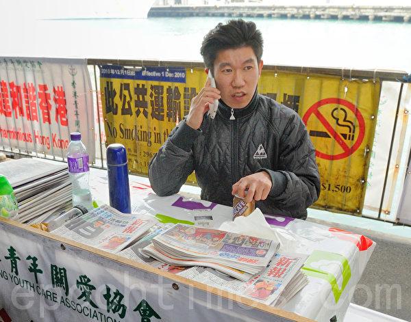 青關會成員在香港尖沙咀天星碼頭派發污衊法輪功的《新報》。(攝影:宋祥龍/大紀元)