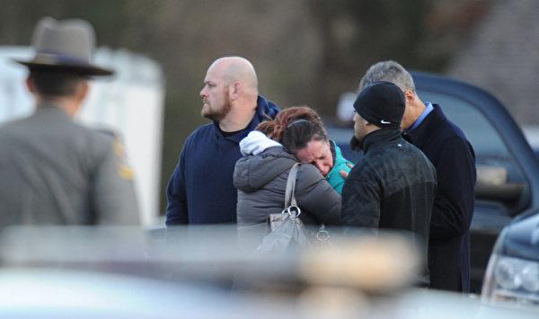 一位女孩在校门外失声恸哭。(图片来源:DON EMMERT/AFP/Getty Images)