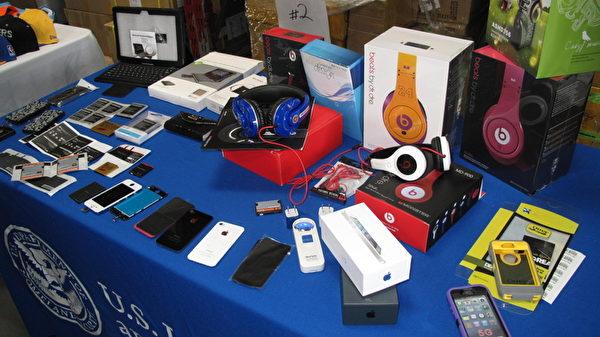 圖:沒收的商品中可以看到有iPhone及手機殼、充電器等配套產品,筆記本電腦、平板電腦,運動衣、鞋帽以及玩具,名牌手袋,DVD等。所有的商品都來自中國和香港。(攝影:劉菲/大紀元)