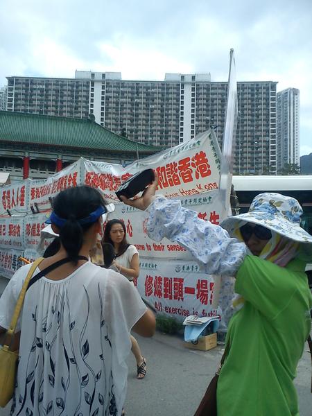 2012年8月1日穿绿衣的大陆邪教协会的帮凶拿着扩音喇叭,滋扰及阻碍法轮功学员与大陆游客交谈。(香港市民提供)