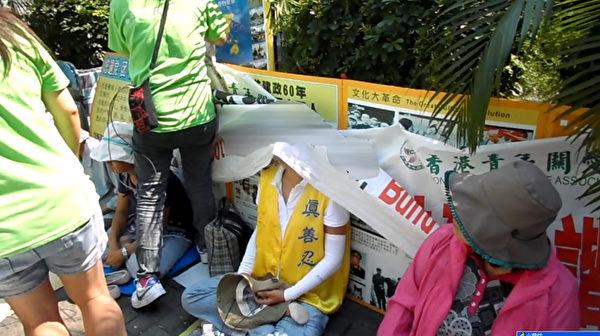 2012年10月3日,青关会徒众侵扰红磡火车站外的法轮功真相点,用诬蔑横幅遮盖真相展板,过程中完全无视静坐中的法轮功学员,把横幅覆盖在学员头上。(大纪元)
