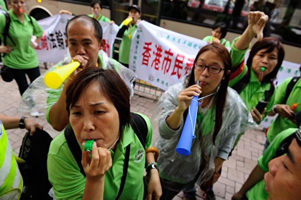 2012年11月25日,青关会团伙捣乱法轮功学员举办的九评退党集会游行。他们每人都佩戴口哨或喇叭,发出刺耳的噪音。(摄影/宋祥龙)