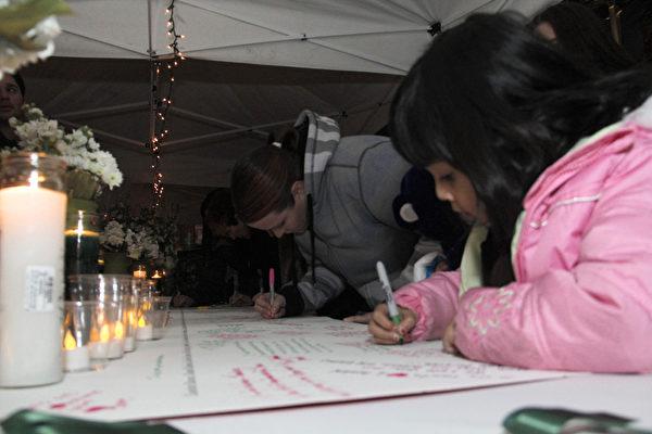 民众在签名处写下自己对康州校园枪击案死难者的祝福(摄影:丘石/大纪元)