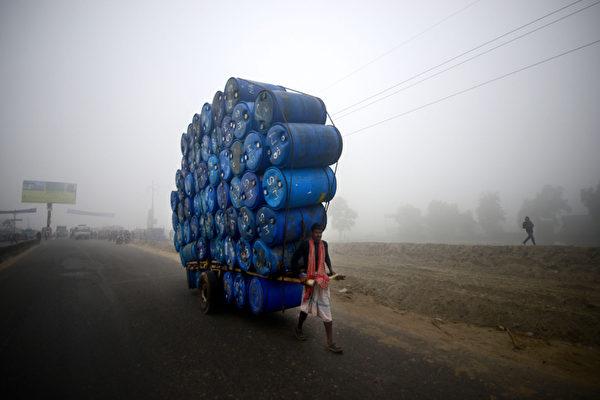 孟加拉国达卡,一名男子拉着一辆载满桶状容器的车。在12个伊斯兰团体的号召下,该国发起了全国范围的大罢工。摄于2012年12月20日。(MUNIR UZ ZAMAN/AFP)