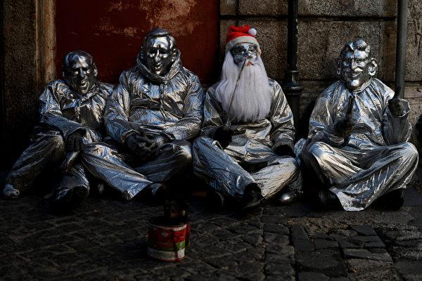 意大利罗马市中心,几人装扮成金属雕像的样子坐在地上,前面放着一个施舍罐。摄于2012年12月19日。(FILIPPO MONTEFORTE/AFP)