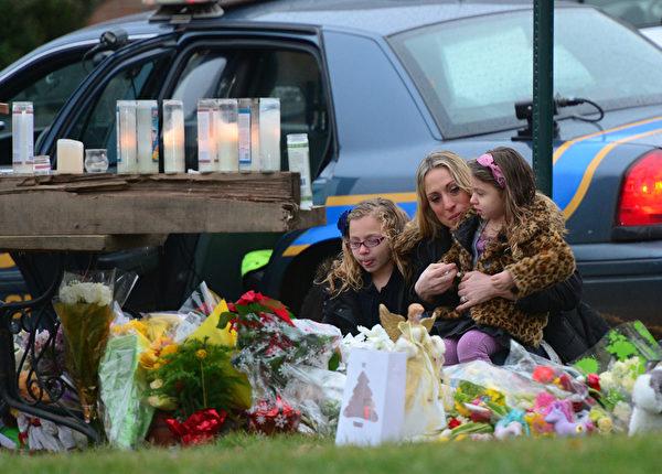美国康涅狄格州纽敦市桑迪胡克(Sandy Hook) 小学12月14日发生重大枪击案后,民众以各种纪念品和鲜花,悼念枪击案的遇难者。摄于2012年12月16日。(EMMANUEL DUNAND/AFP)