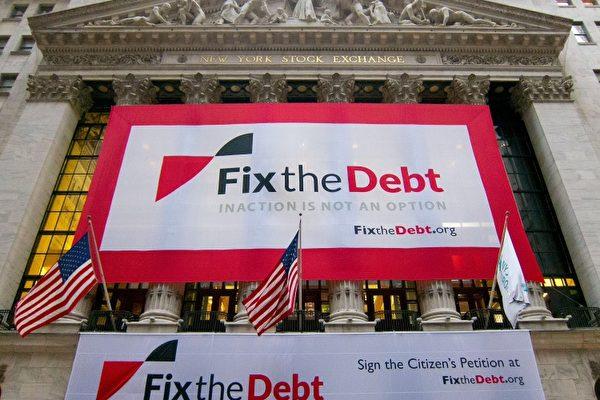 """图:""""解决债务运动""""在纽约证券交易所大楼上悬挂的横幅:不作为不是选项。呼吁立即采取措施,合力解决财政赤字问题。(图片由解决债务机构提供)"""