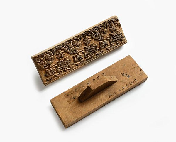 唐衣的金箔樣本(1837年):為製作唐衣上的花紋,在木板上刻出「壽」、「福」字樣和石榴花紋。經確認這個金箔樣本和德惠翁主所穿唐衣肩膀處的花紋極為相似。(照片提供:國立故宮博物館)