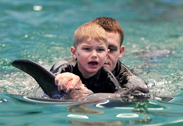 图为一自闭儿童接受海豚治疗 (VIKTOR DRACHEV/AFP/Getty Images)
