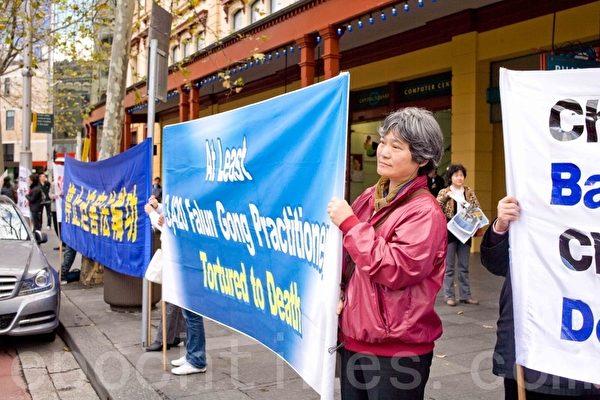 在雪梨中国城打横幅的法轮功学员。(摄影:袁丽 / 大纪元)