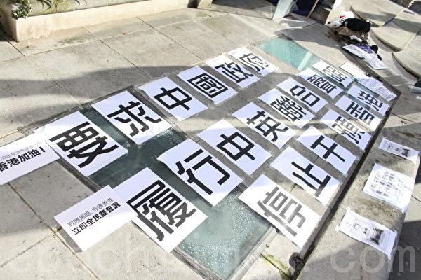 參加集會的港人,把他們的訴求寫得大大的并整齊地帖在地上。(攝影: 李瑩/大紀元)