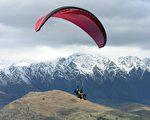 从事飞行伞活动的游客在天空中翱翔。(Photo by PAUL ELLIS / AFP)