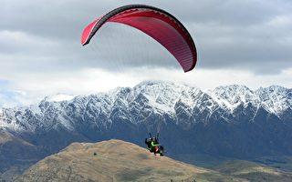 從事飛行傘活動的遊客在天空中翱翔。(Photo by PAUL ELLIS / AFP)