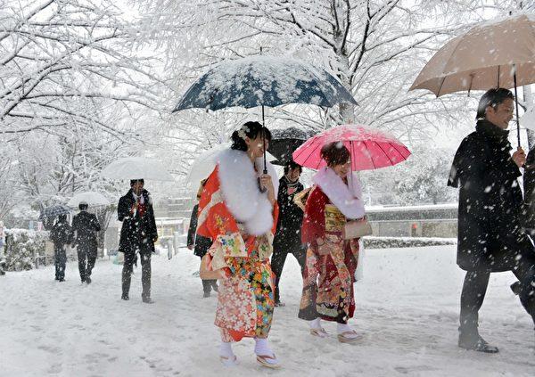 2013年1月14日,东京都心降下今年冬天第一场雪。图为身穿和服的20岁妙龄女子前往参加东京的成年仪式。(Yoshikazu TSUNO/AFP)