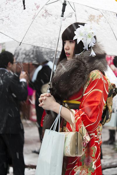 成人节当天,女子必著和服,拎挎箱包,佩戴头饰,精心装扮一番。(摄影:梁超人/大纪元)