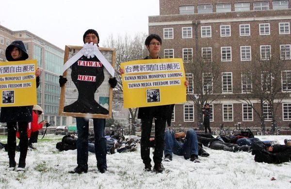 """台湾留英学生在雪地中上演""""噤声、躺下、新闻自由死亡""""行为艺术反对媒体垄断。(摄影:大纪元/李莹)"""