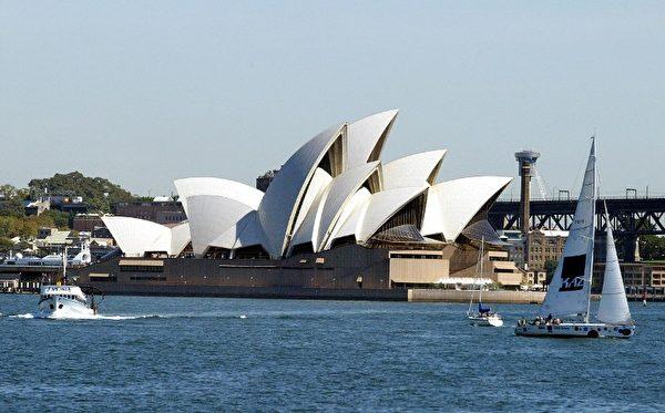 在碧海蓝天的衬托下,雪梨歌剧院的白色贝壳状屋顶显得十分耀眼。(Photo by ROB ELLIOTT / AFP)