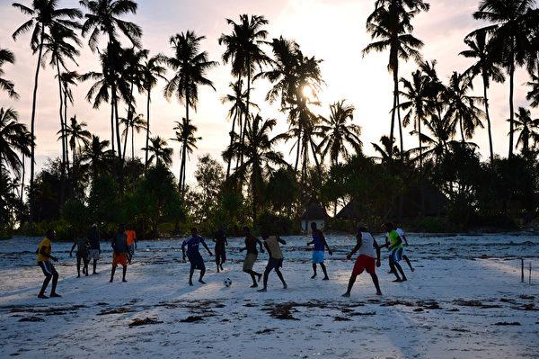 桑吉巴居民在海滩玩足球。(GABRIEL BOUYS/AFP)