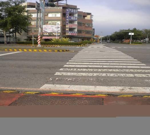 在市區友忠路與自由路口的行人穿越道,原有行人穿越道行經分隔島處有約20公分的高低差障礙,改善前如圖。(嘉義市政府交通處提供)