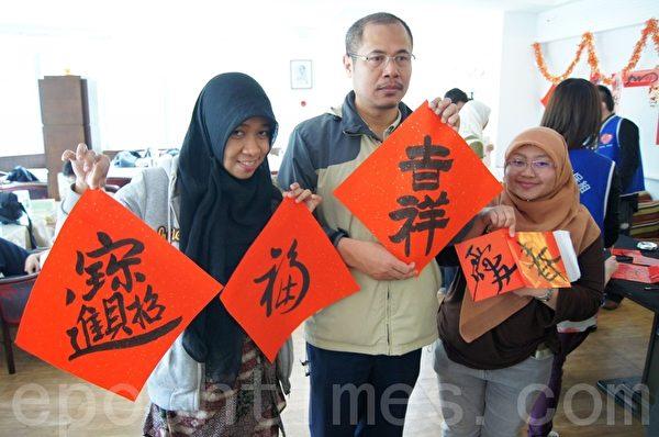 來自印尼的國際學生身著中國傳統服飾,體驗揮毫寫春聯的樂趣。(攝影:徐乃義/大紀元)