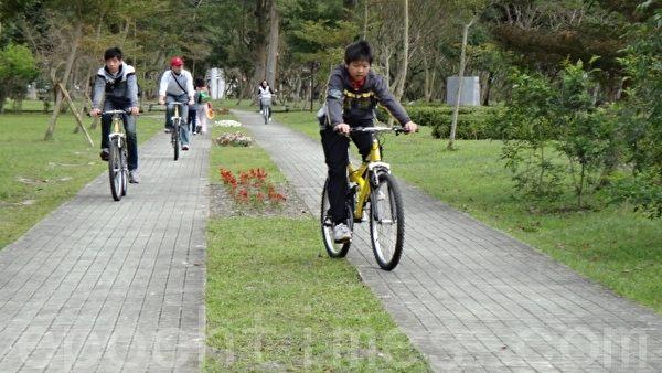 亲子骑乘自行车环绕鲤鱼潭湖畔。(摄影:詹亦菱/大纪元)