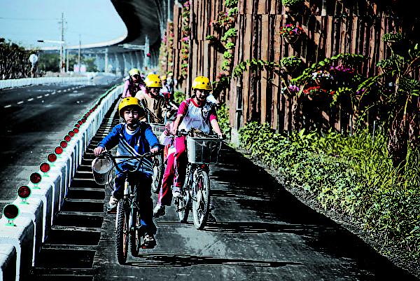 二高高速公路下,一望无际的绿色廊道,是全台独一无二的单车国道。(图:屏东县政府提供)