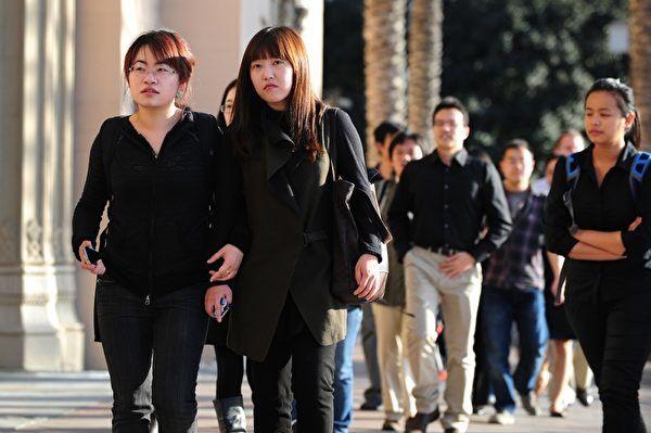 """近几年美国经济的不景气,促使大批美国私立中学扩招国际学生,从而引发了新一波中国高中学生赴美留学热潮。可是,随着大量中国学生的涌入,许多学校又不得不面对 """"人满为患""""的难题。图为美国的中国留学生。(Frederic J. BROWN/AFP)"""