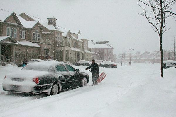 加拿大雪暴7日晚开始在大多伦多区肆虐,持续到8日,给多伦多带来25到30厘米积雪。路上不少汽车在雪里抛锚,司机不得不自己拿雪橇铲雪开路,同时等待铲雪车救援。(摄影:李佳/大纪元)