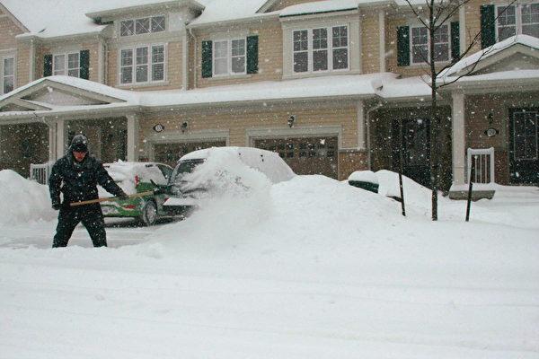加拿大雪暴7日晚开始在大多伦多区肆虐,持续到8日,给多伦多带来25到30厘米积雪。小区内居民正在自家们口清理积雪。(摄影:李佳/大纪元)