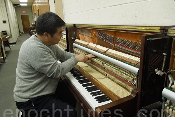 韩裔钢琴调音师吴英玄先生正在维修钢琴。(摄影﹕杨琼宇/大纪元)